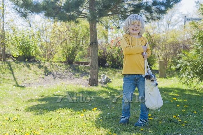 Boy carrying Jack Russel Terri・・・