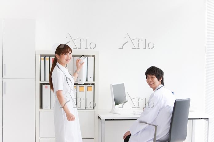 座っている医師とカルテを取る看護師