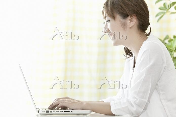 笑顔でノートパソコンを操作する若い日本人女性