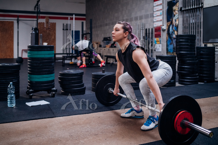 Young woman lifting barbell in・・・