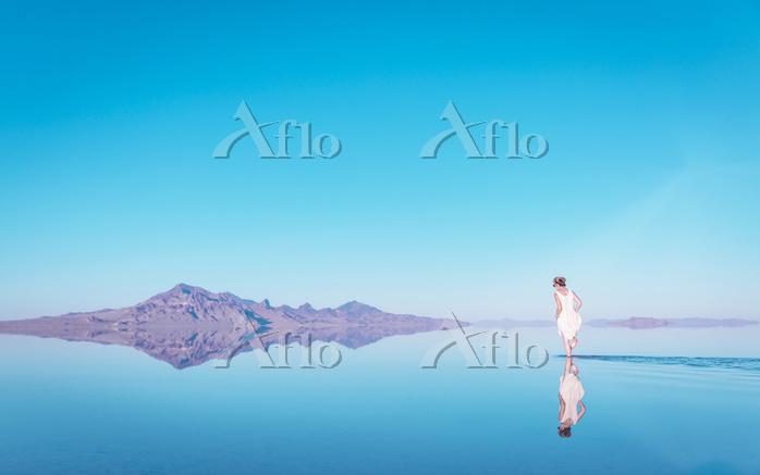 Woman walking in lake by mount・・・