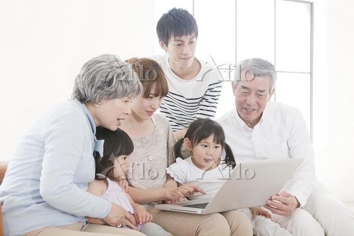 ソファに座りノートパソコンを見る日本人の三世代家族