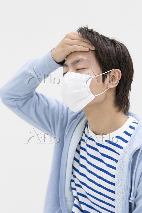 マスクをして額に手をあてる若者日本人男性
