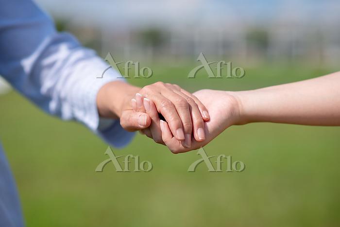 手をつなぐ女性の手元