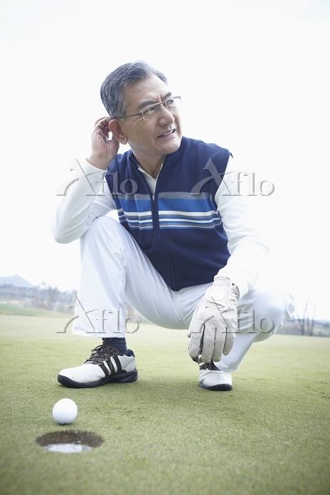 ゴルフをするシニア男性