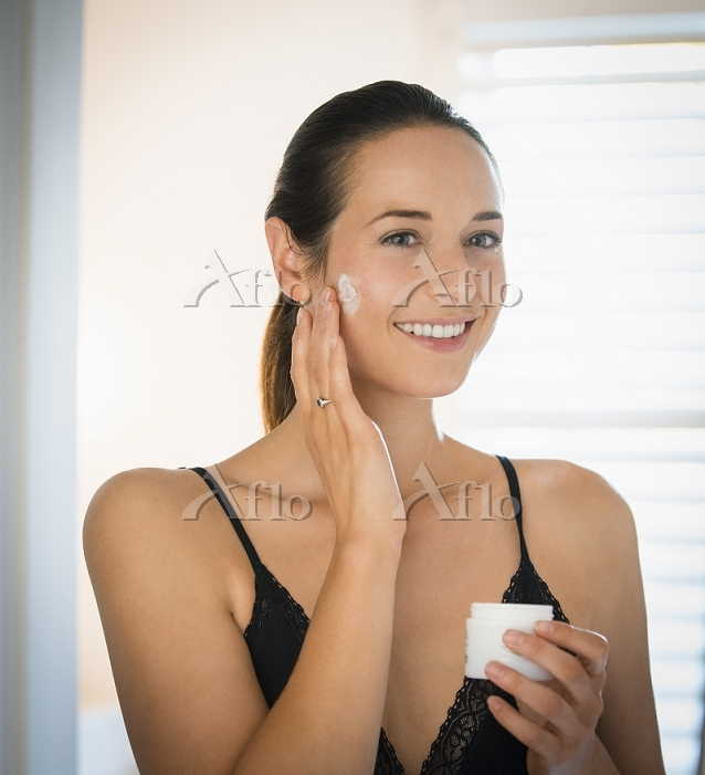 Smiling woman applying face cr・・・