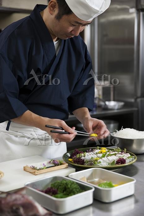 鯛の松皮造りを盛り付ける調理師