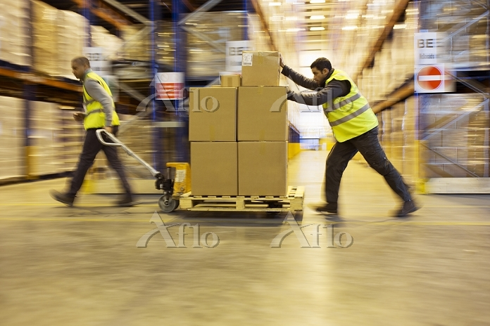 Workers carting boxes in wareh・・・