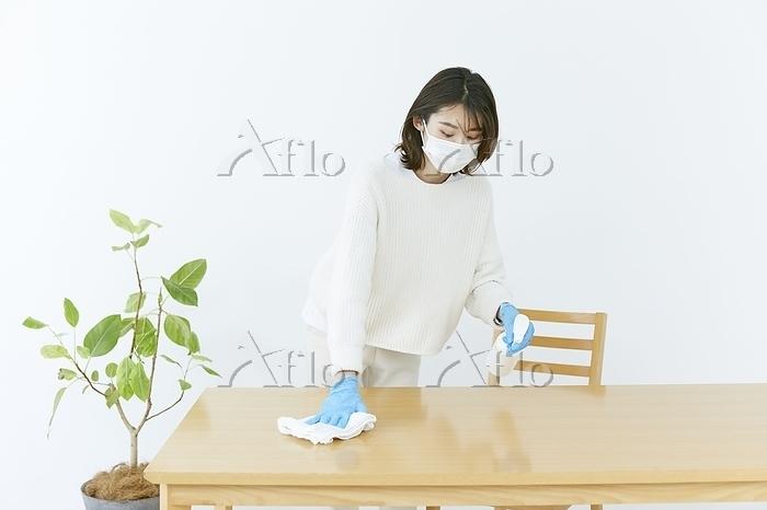 テーブルの除菌をする日本人女性