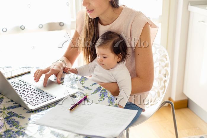 Mother working on laptop with ・・・