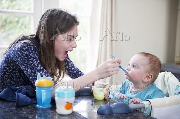 赤ちゃんに食事を与えるお母さん