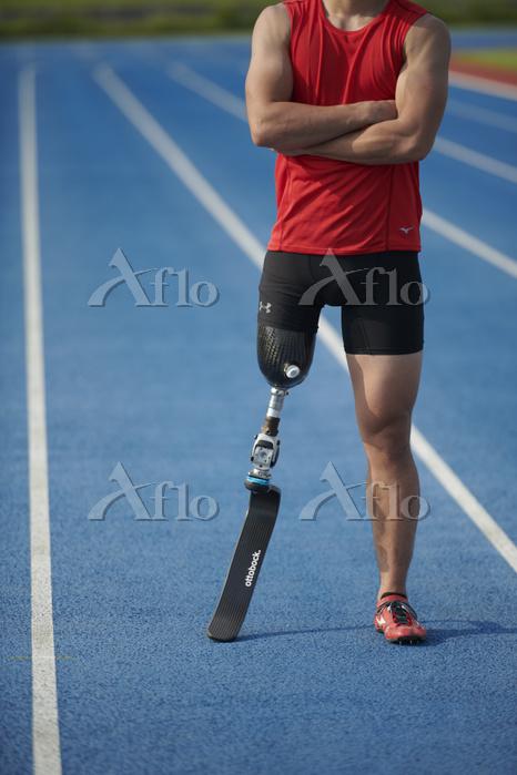 腕を組む義足陸上競技選手