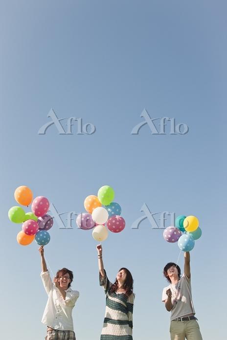 風船を持つ若者たちと青空