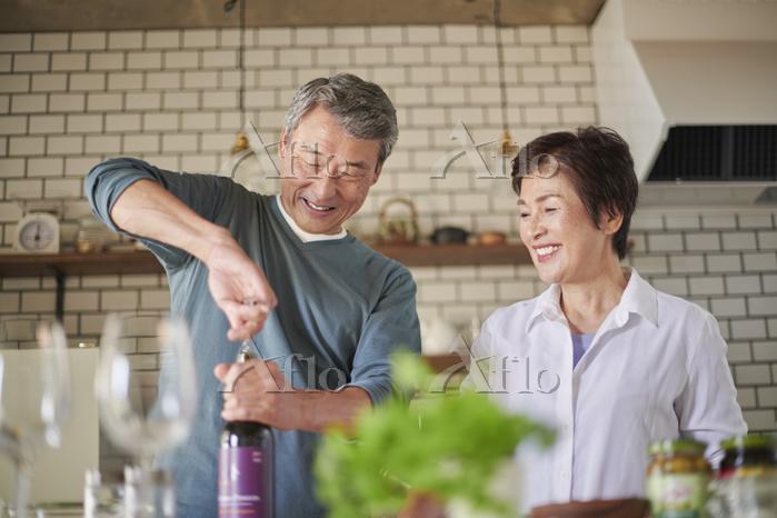 ワインを開ける日本人のシニア夫婦