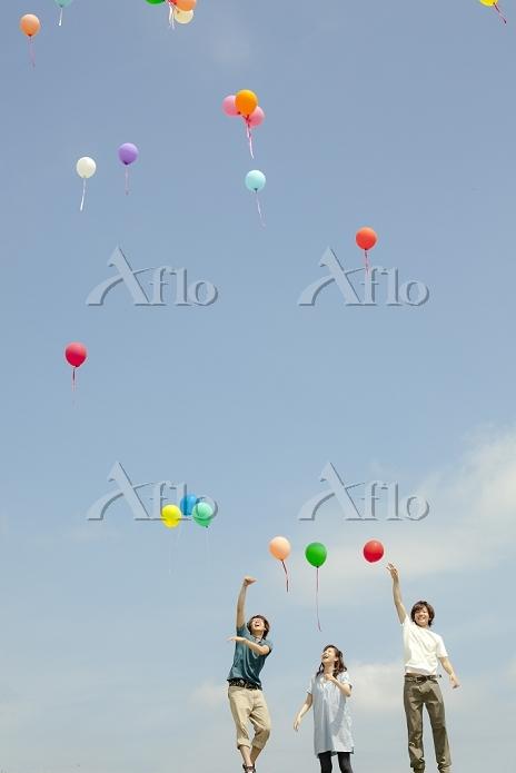 青空に風船を飛ばす若者たち