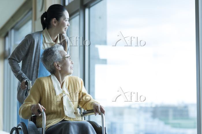 車椅子の老夫婦を介助するホームヘルパー