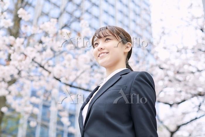 桜とスーツを着た日本人女性