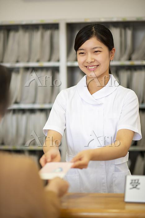 お薬手帳を渡す女性職員