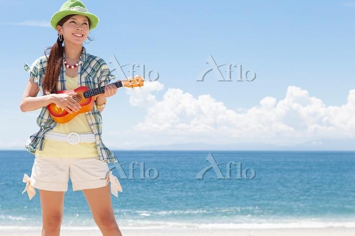 海岸でウクレレを演奏している日本人女性