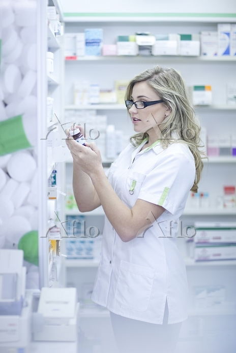 Pharmacist looking at box of m・・・