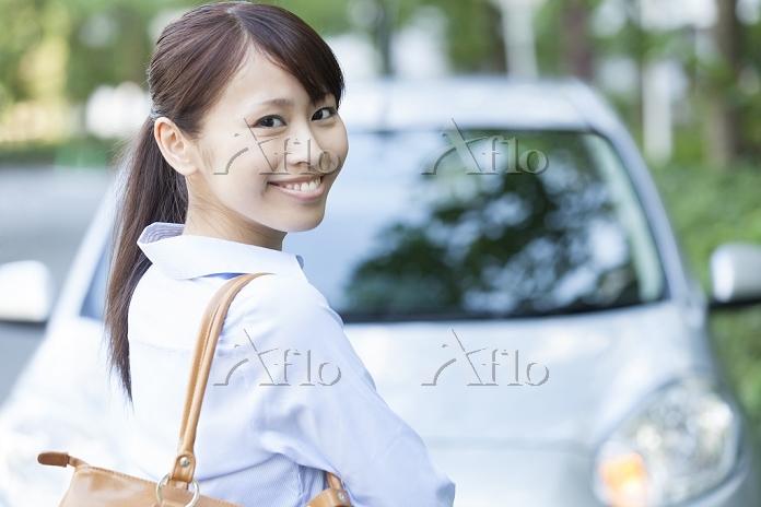 車の前で微笑むビジネスウーマン