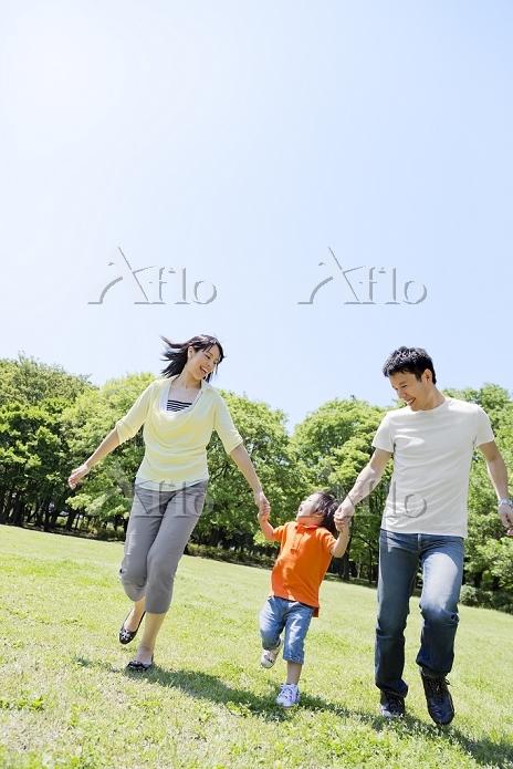 公園を手を繋いで歩く日本人三人家族
