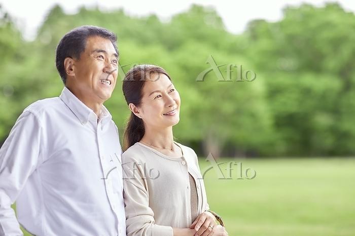 公園を散歩する日本人シニア夫婦