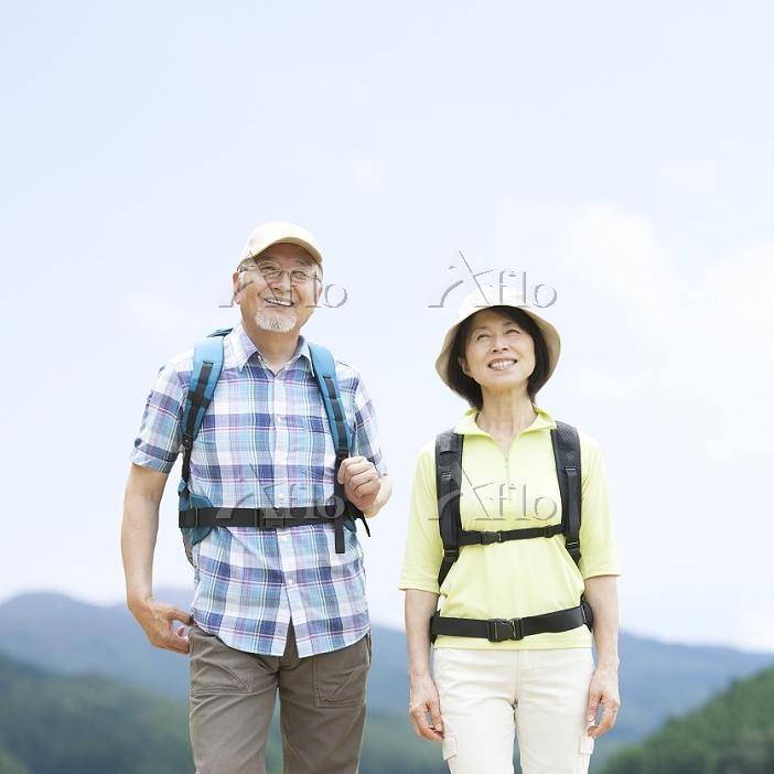 リュックを背負って歩くシニア夫婦