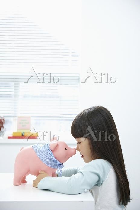 A girl facing a pink piggy ban・・・