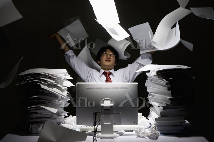 書類をばらまく若い男性