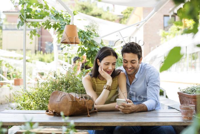 カフェテラスでスマホを見る夫婦