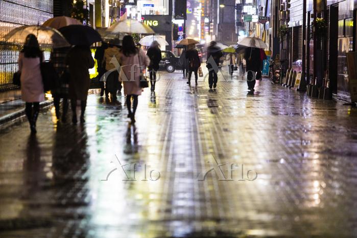 雨の都心の街並みと歩行者