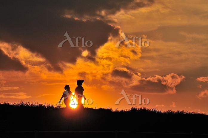 夕日の土手を散歩する子供のシルエット