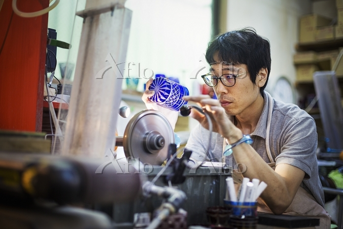 ガラス加工をする職人の男性