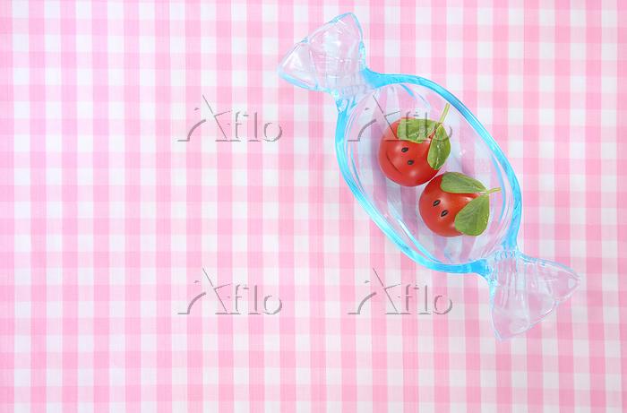 顔のあるかわいいミニトマトのカップルとキャンデイ型のガラス皿