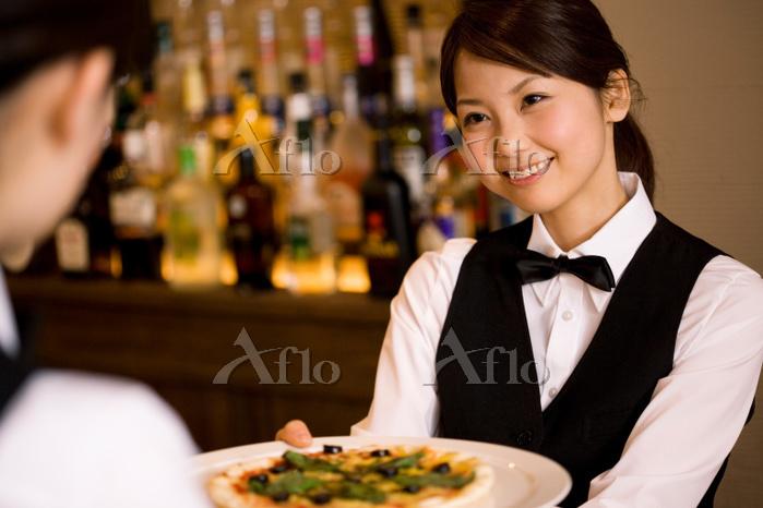 ピザを渡す日本人女性従業員