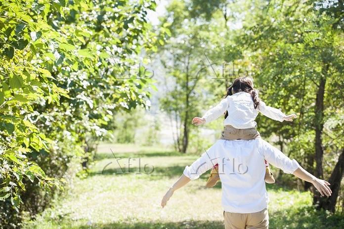 緑の中で手を広げる親子