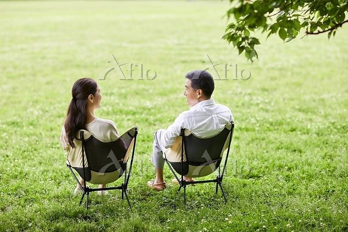芝生でくつろぐ日本人シニア夫婦