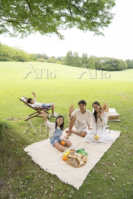 ピクニックに来た公園で寛ぐ家族