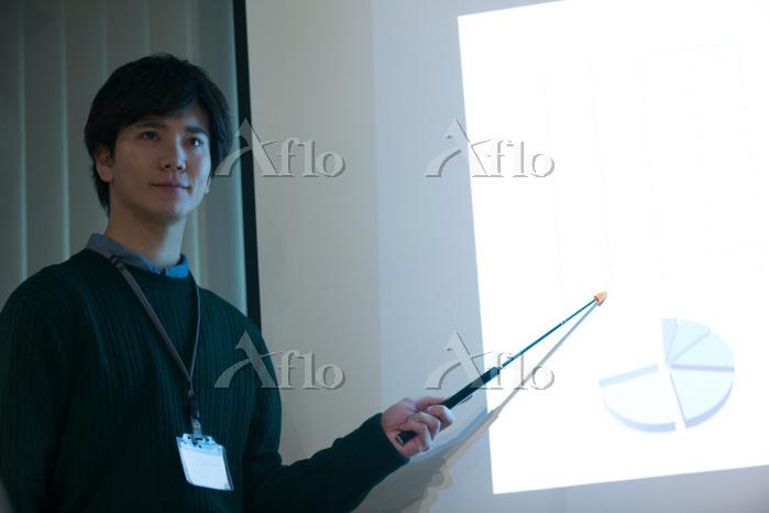 会議で説明をする日本人男性