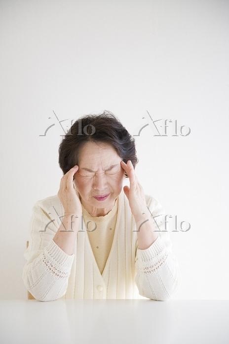 こめかみを押さえる年配の女性