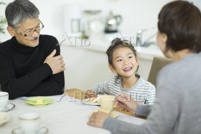 孫とおやつを食べる日本人のシニア夫婦