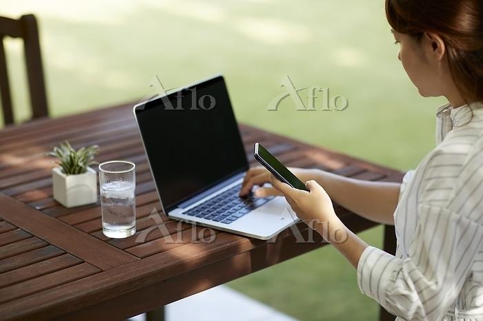 スマホとノートPCを操作する日本人女性