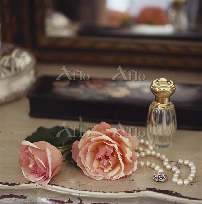 バラと真珠のネックレスと香水ボトル