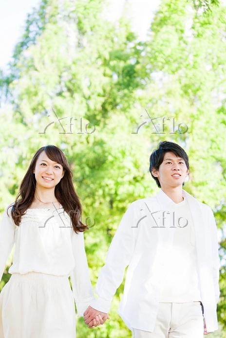 新緑の中で手を繋ぐカップル