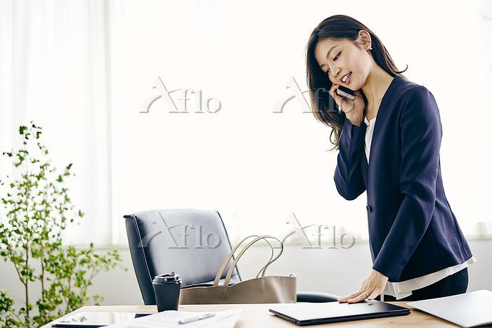スマートフォンで話す30代ビジネスウーマン