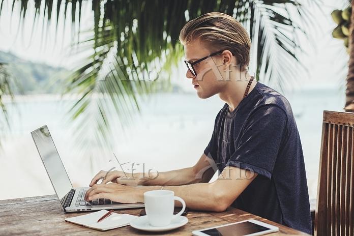 カフェでラップトップを使う男性