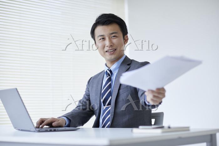 書類を渡す日本人ビジネスマン