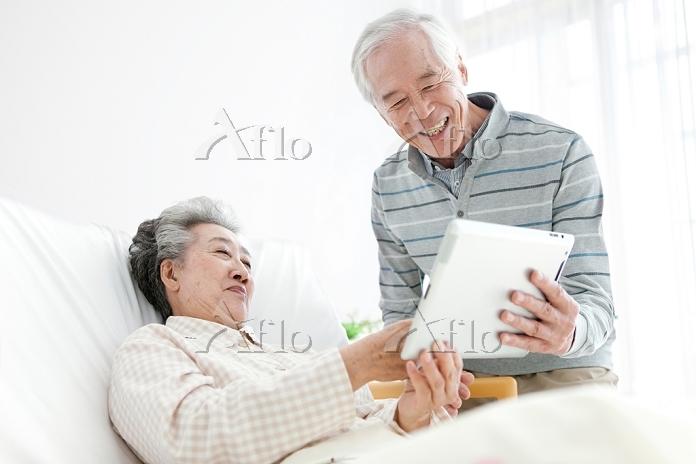 タブレットを操作する中高年夫婦