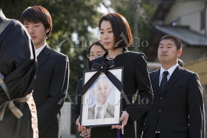 遺影を持つ日本人女性と遺族